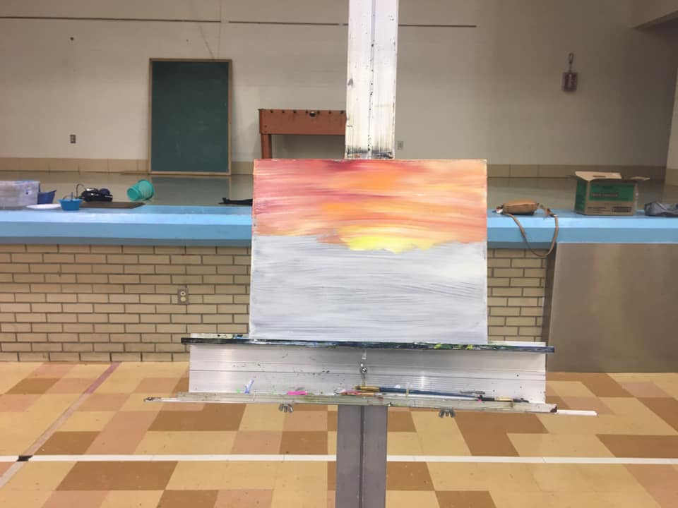 students paints a sunset at art night