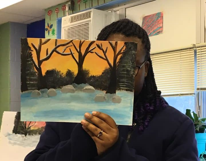 student shows off his watercolor forest painting