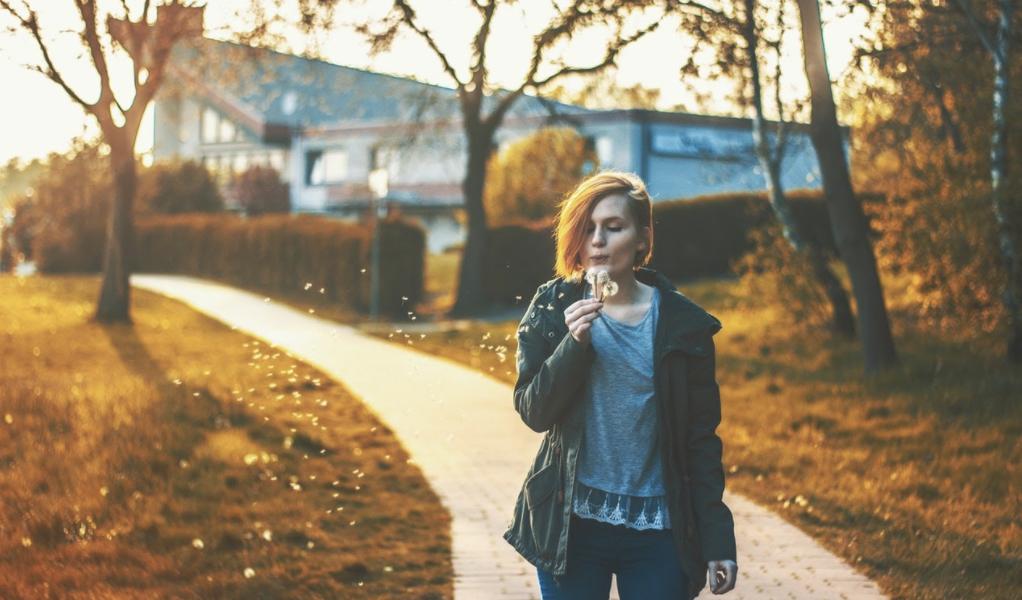 optimistic girl blowing a dandelion